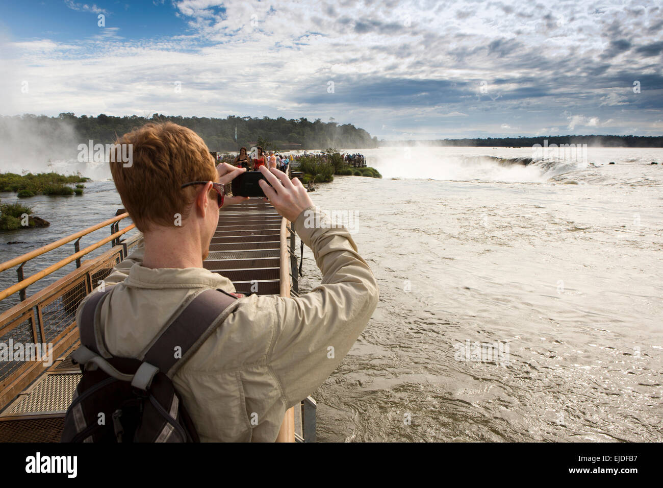 Argentina, Iguazu Falls National Park, tourist taking picture of Garganta el Diablo waterfall, from elevated walkway - Stock Image
