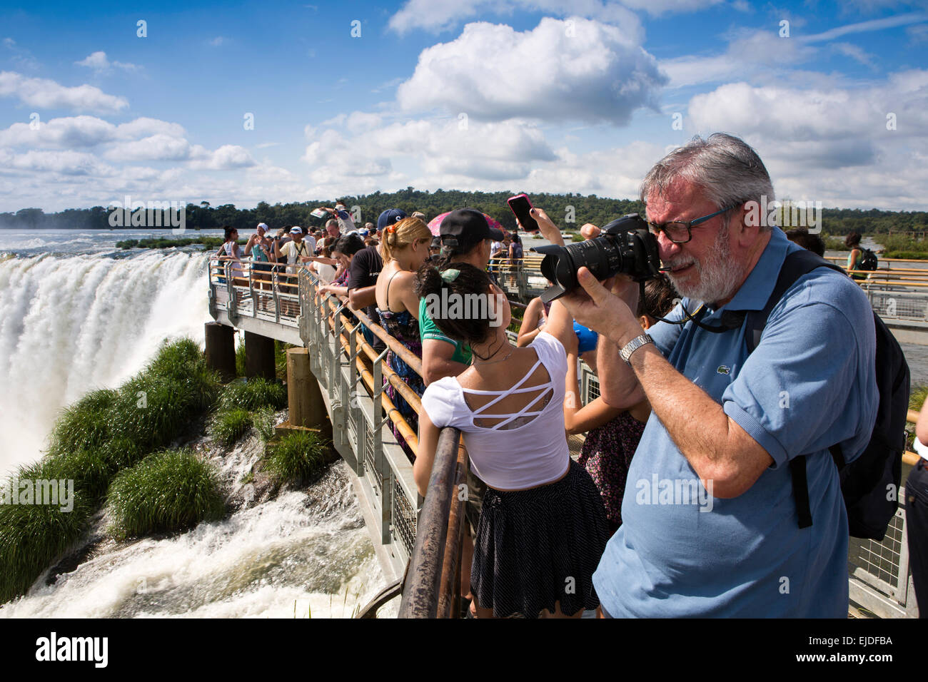 Argentina, Iguazu Falls National Park, tourist talking picture of Garganta el Diablo waterfall, from elevated viewpoint - Stock Image