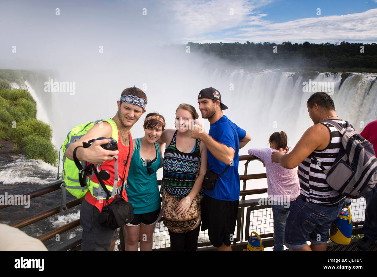 Argentina, Iguazu Falls National Park, tourists taking selfie at Garganta el Diablo waterfall viewpoint - Stock Image