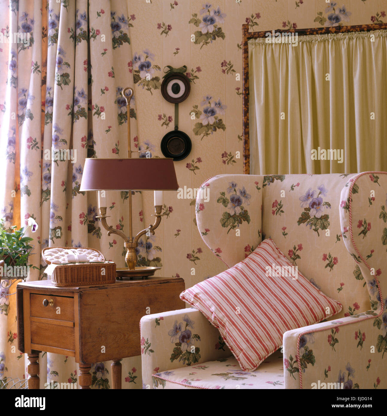 Striped Cushion On Floral Wing Chair In Nineties Bedroom With Stock