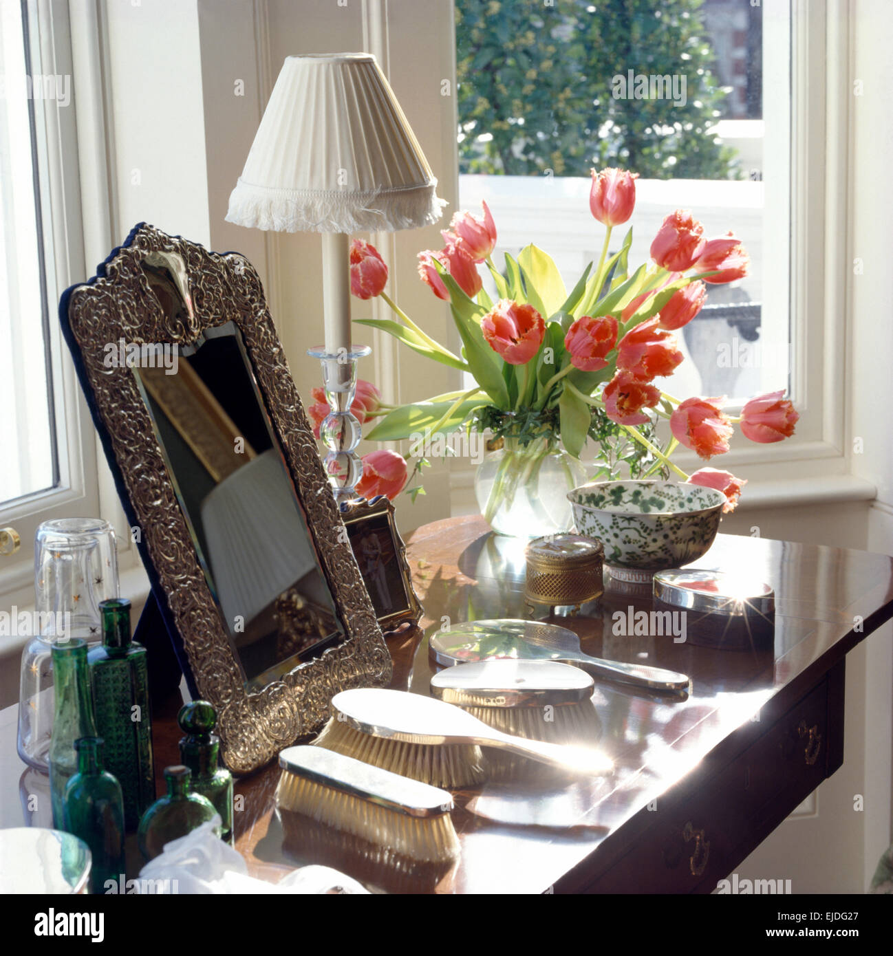 Close-up of silver framed mirror and silver vanity set with vase of red tulips on dressing table - Stock Image