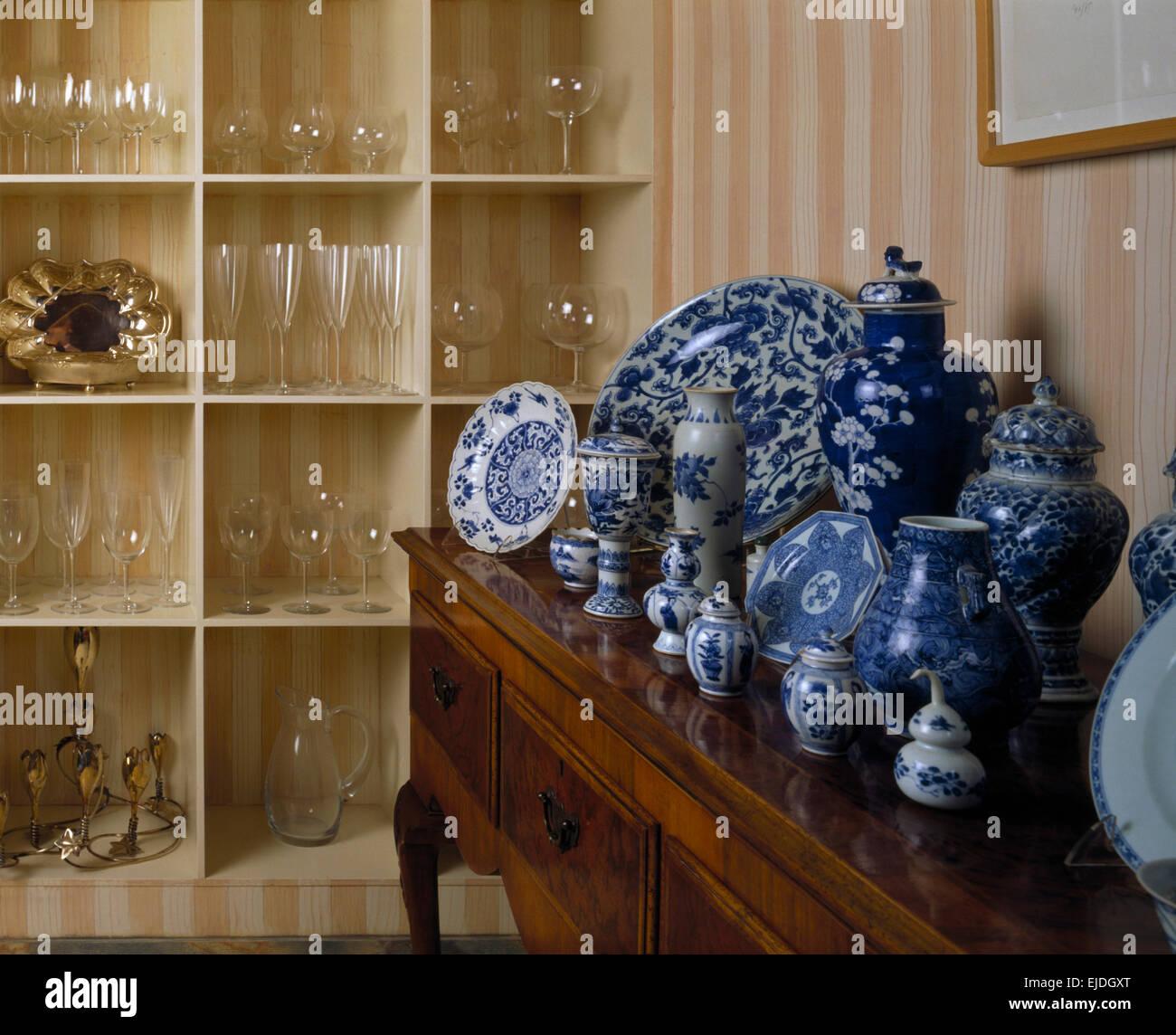 Collection of blue+white Chinese ceramics on antique side table in dining room with glassware on cube shelving Stock Photo