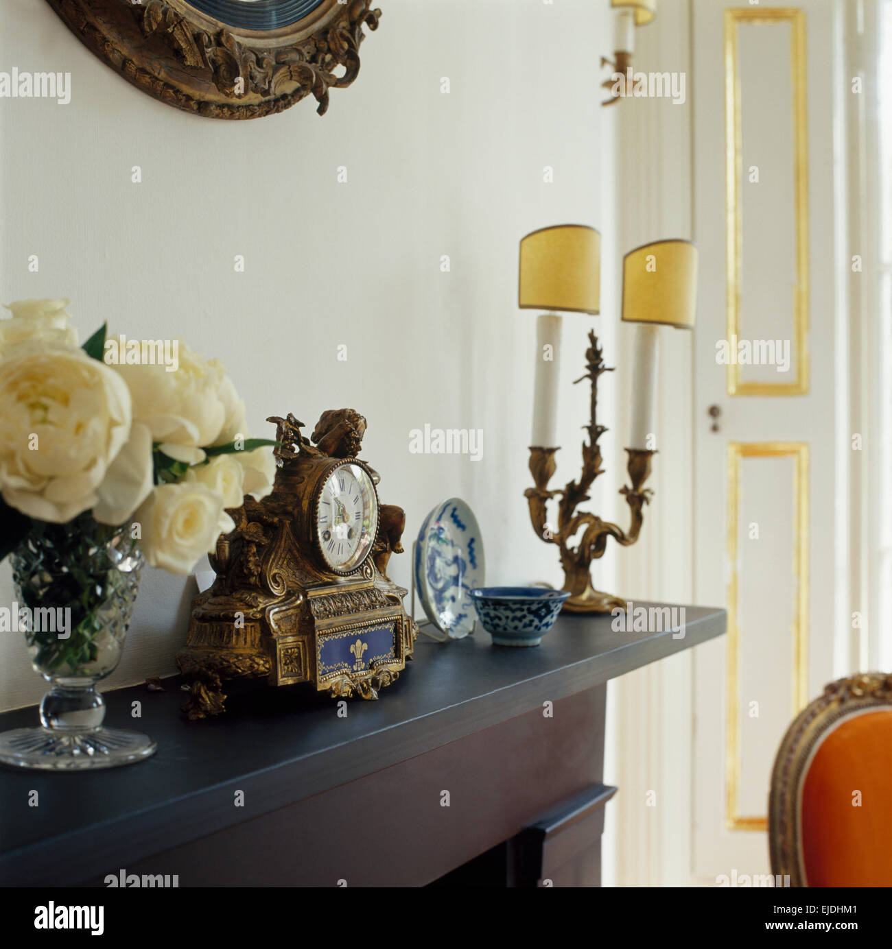 Close-up of a vase of white roses and antique clock on mantelpiece with a vintage brass candlestick - Stock Image