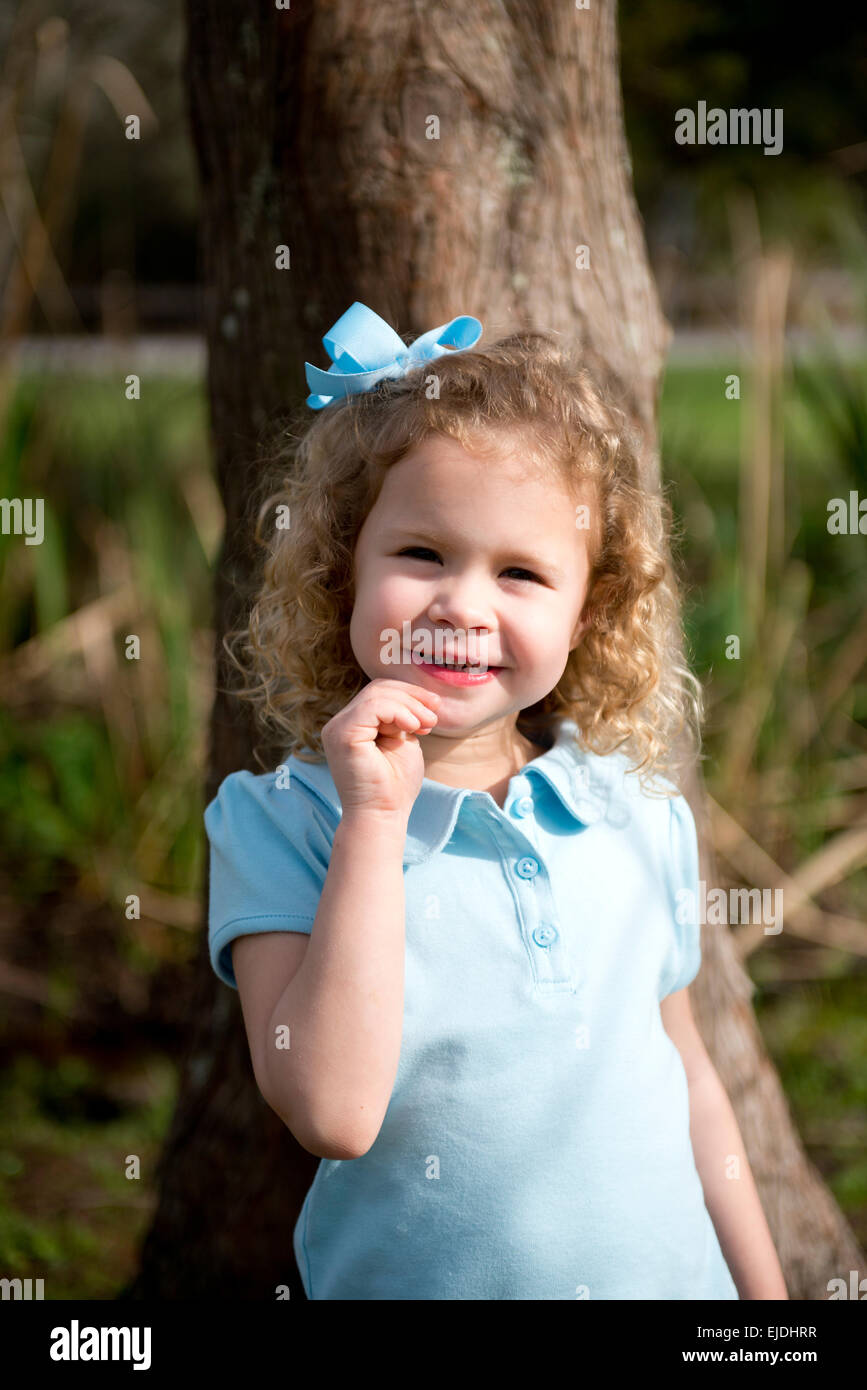 Young girl leaning against oak tree, portrait Stock Photo