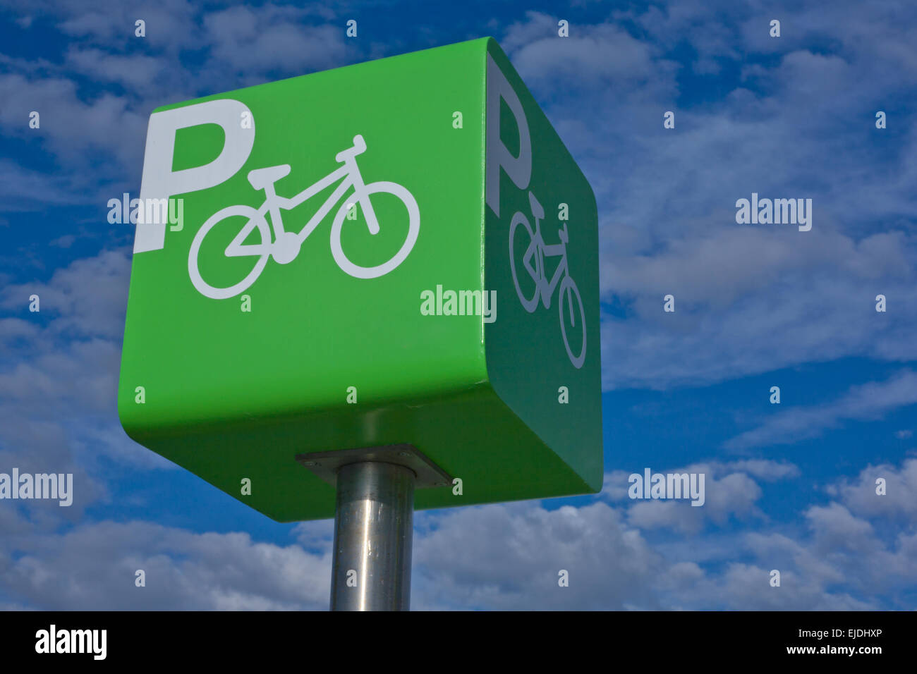 Green parking bicycle pole sign iver blue cloudy sky background Stock Photo