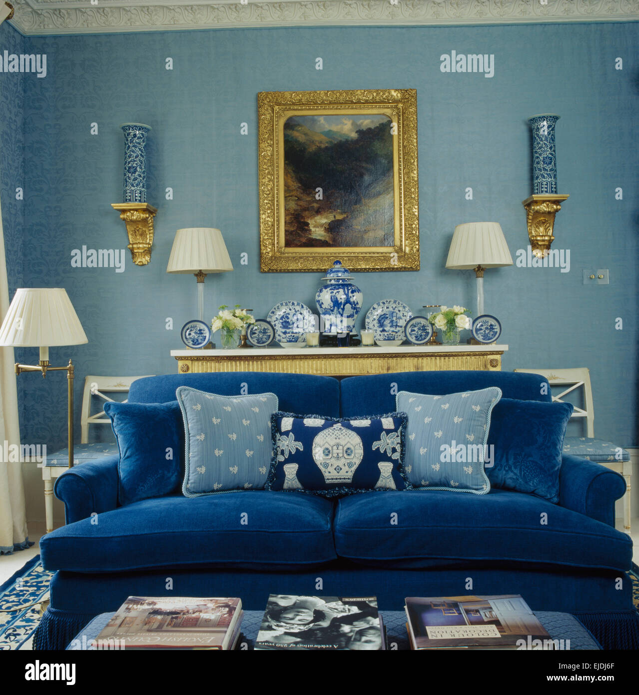 Ordinaire Gilt Framed Picture On Wall Behind Cobalt Blue Sofa With Toning Blue  Cushions In Blue Living Room With Small Gilt Shelves