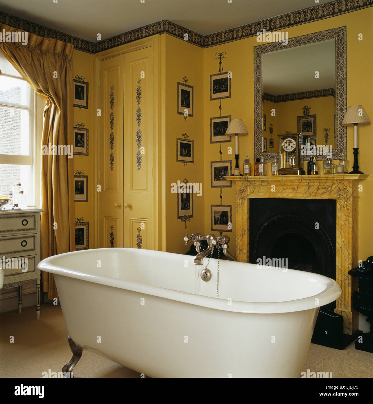 Print room wallpaper in yellow bathroom with roll top bath in front ...