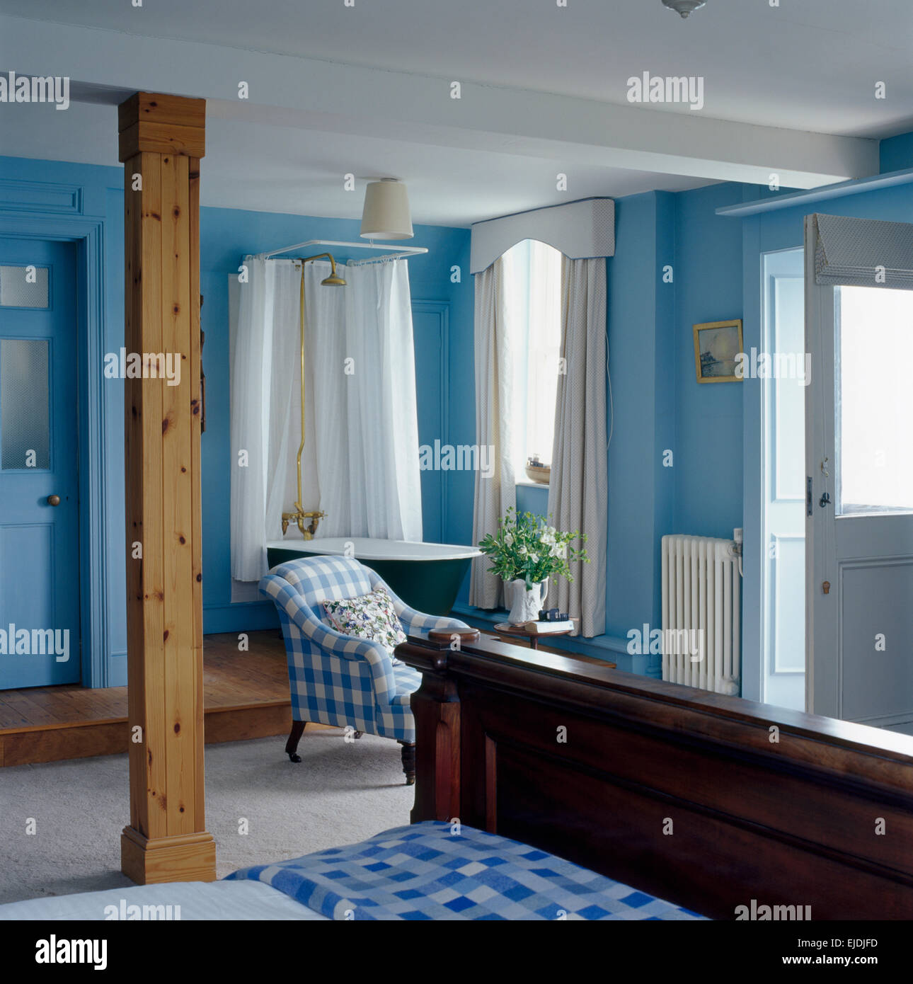 Upright wooden beam in blue coastal bedroom with shower above roll ...