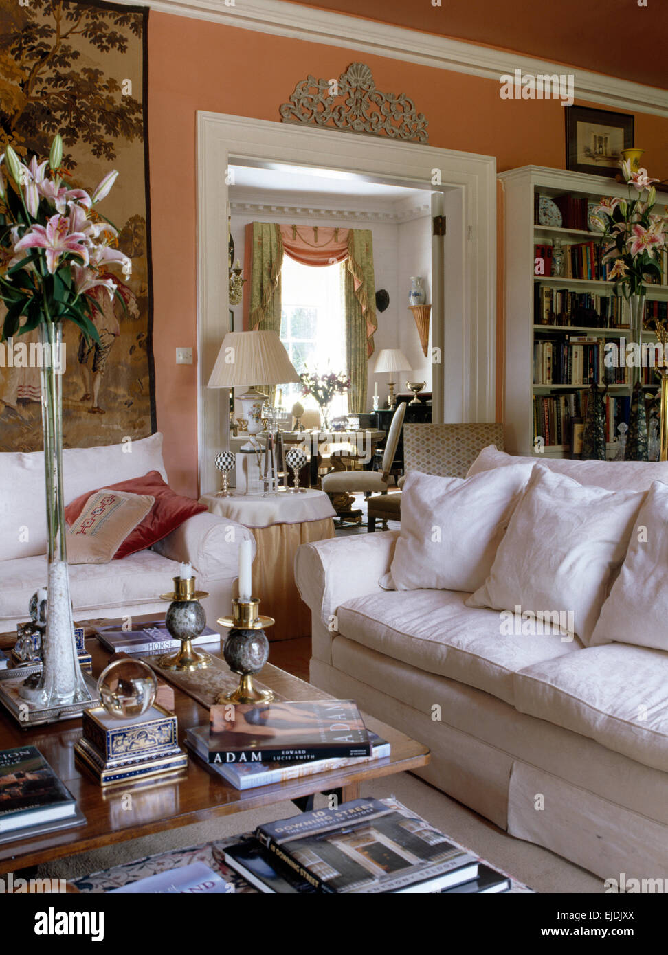 White sofas in traditional peach sitting room with pink lilies in a tall glass vase on the coffee table - Stock Image