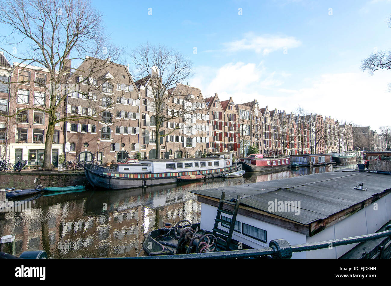 Brouwersgracht Canal in Amsterdam on a sunny day in winter.  A view of canal boats and barges & converted red - Stock Image