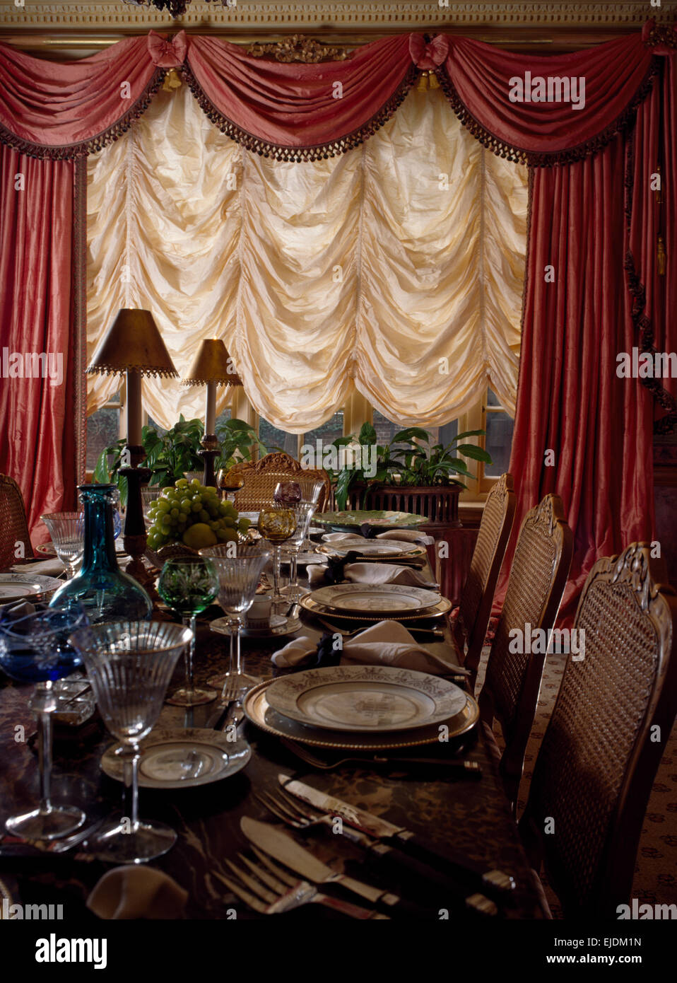 Cream festoon blind and pink swagged curtains in early nineties dining room - Stock Image