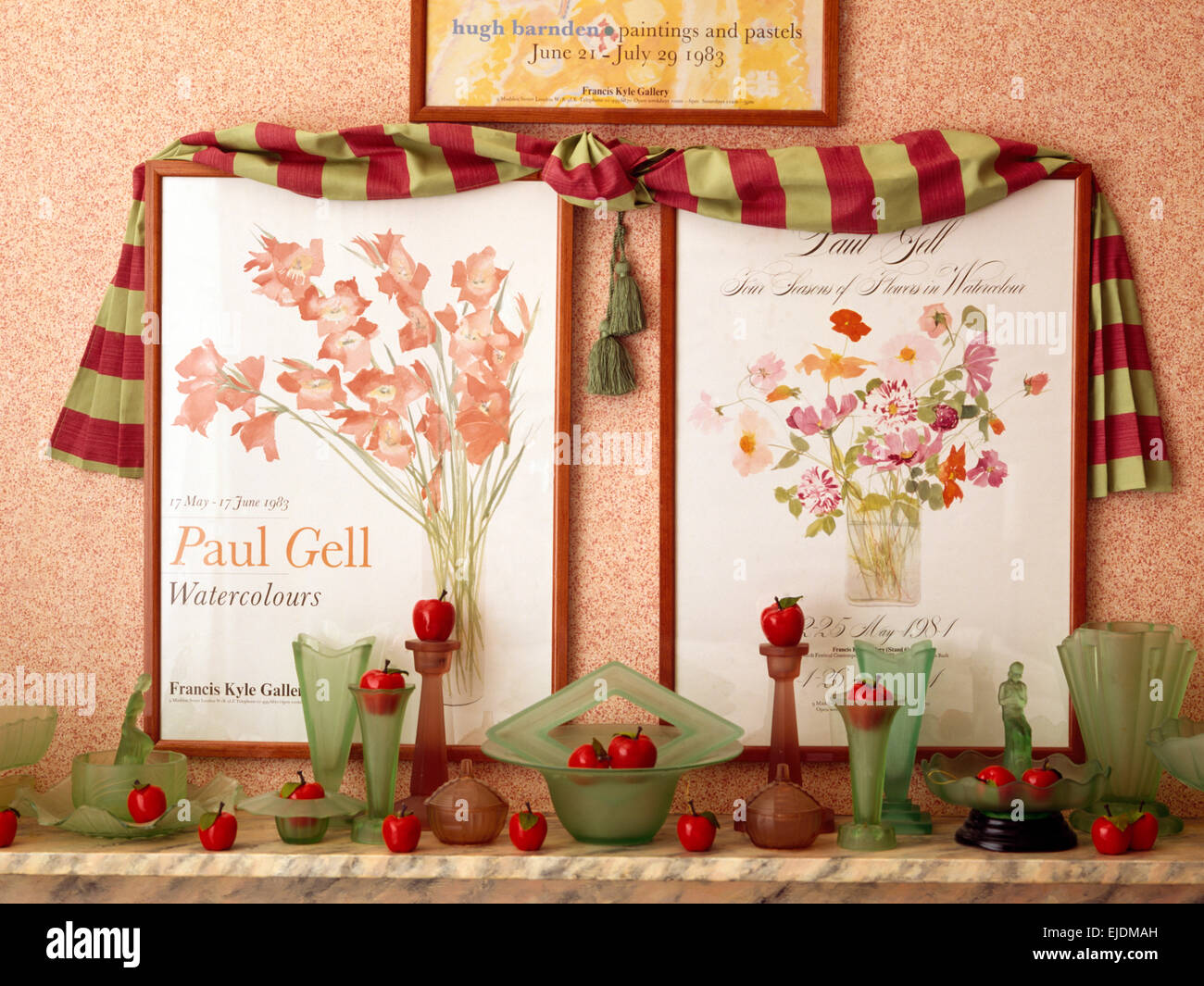 Draped fabric and two floral posters above shelf with collection of vintage glassware - Stock Image
