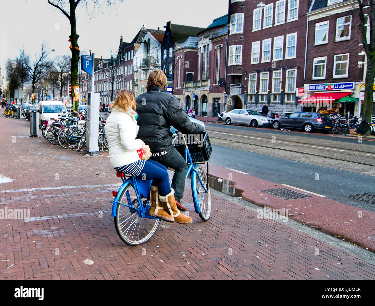 Young girl rides sidesaddle on the back of a boy's blue bicycle on the streets of Amsterdam in the Netherlands. - Stock Image