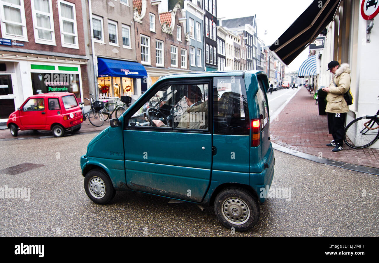 Tiny blue micro-car called a Canta on the streets of Amsterdam. No driving license is required for these vehicles. Stock Photo