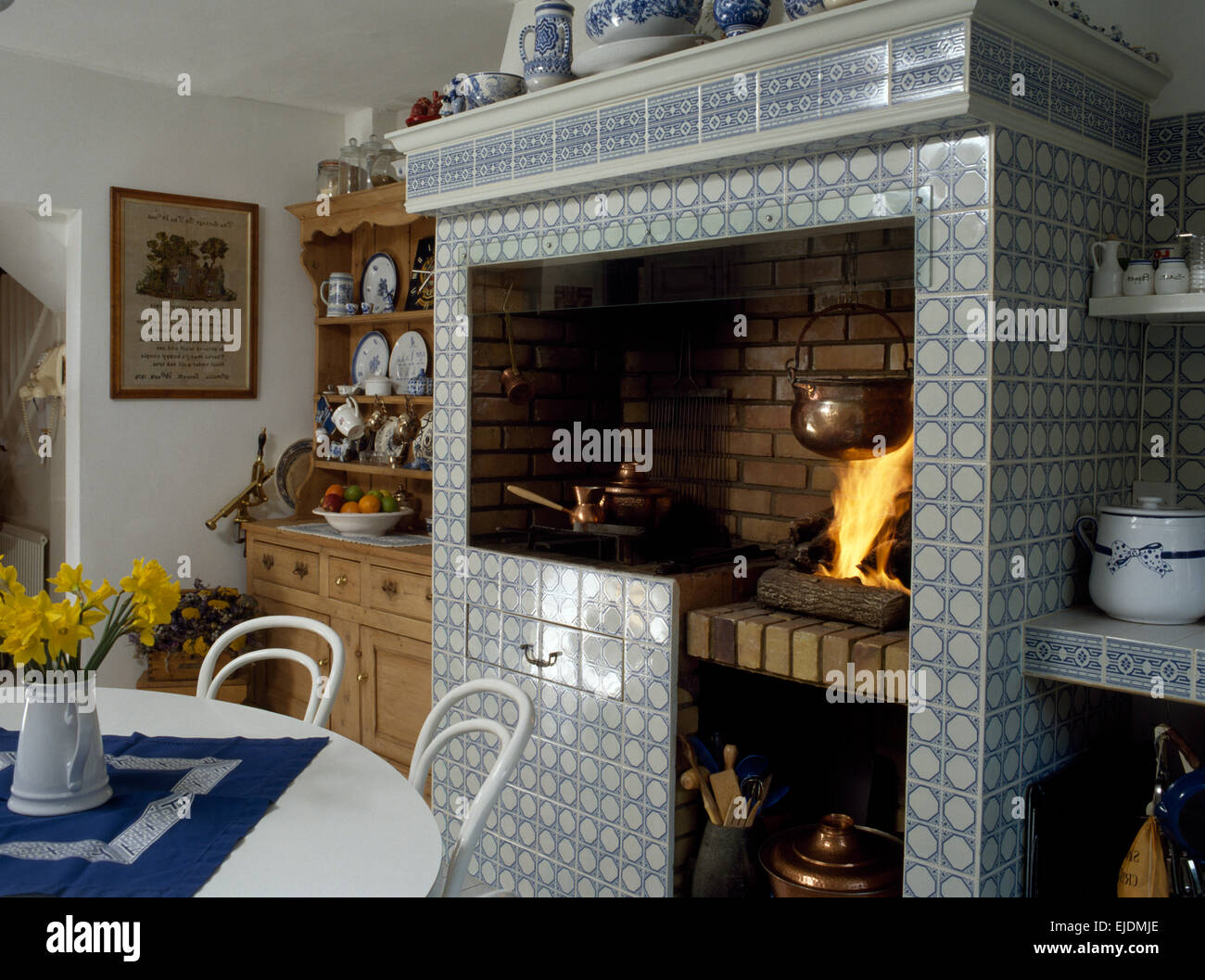 Lighted fire in blue+white tiled fireplace in eighties kitchen dining room Stock Photo