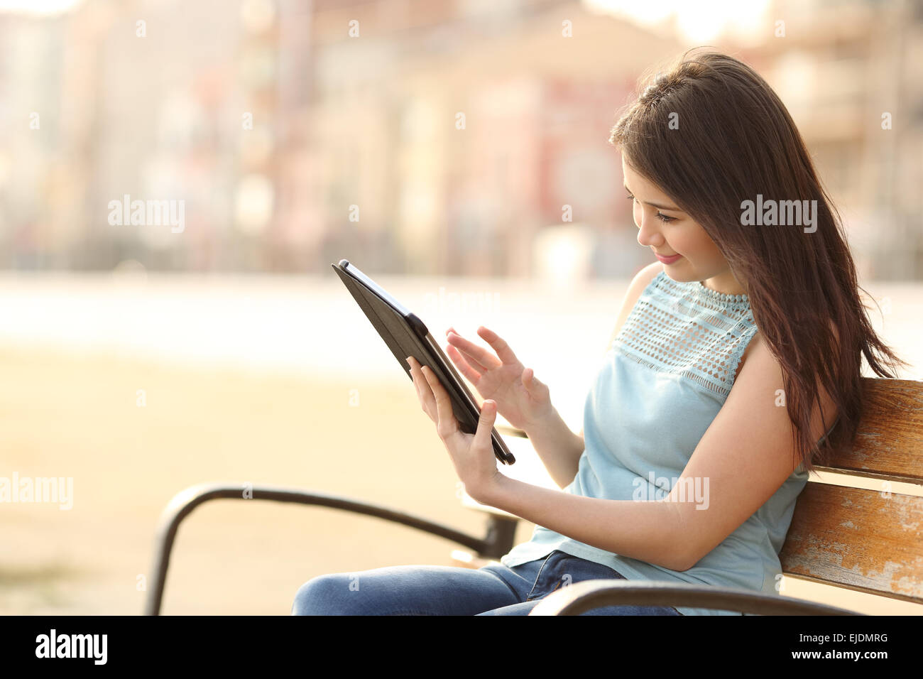 Girl reading and browsing an ebook or a tablet sitting in a bench in a park - Stock Image