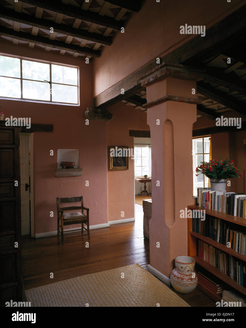 Pink washed walls in hallway in open-plan Mexican house - Stock Image