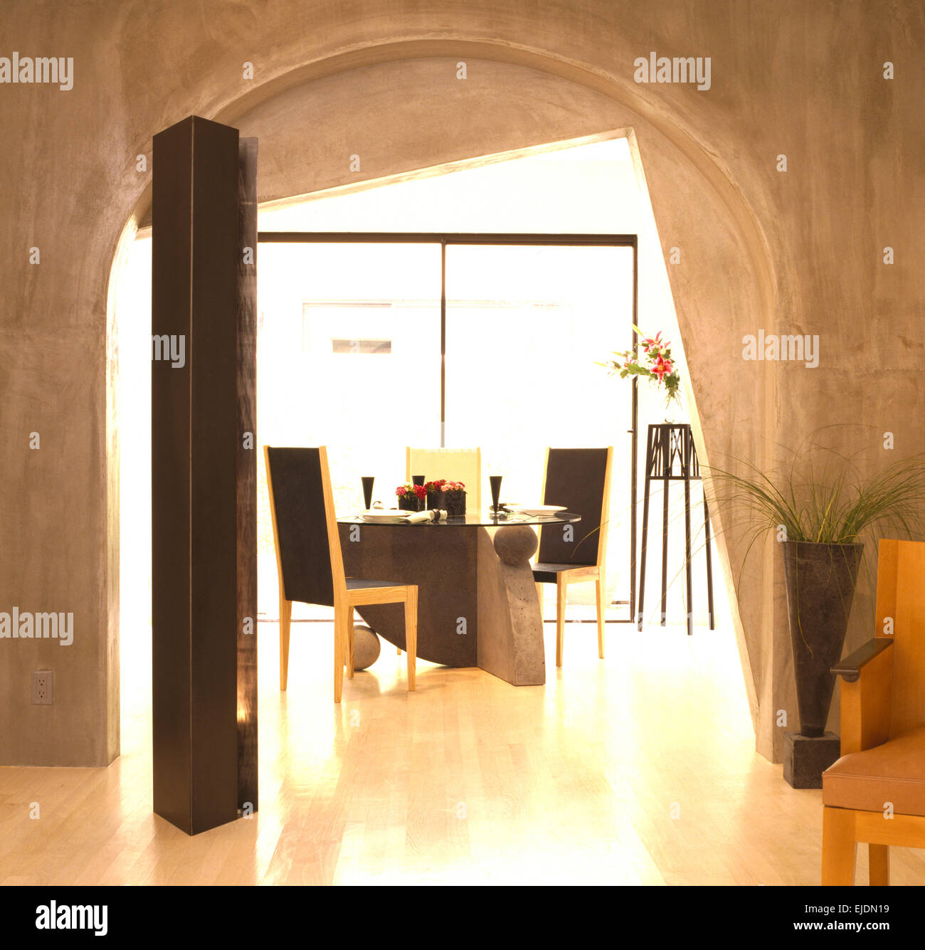 Concrete walls and polished floor in dining area with arched doorway and tall speaker in late eighties Californian - Stock Image