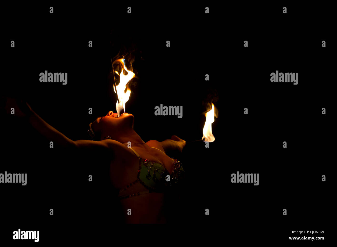 A fire breather woman is eating fire and flames - Stock Image