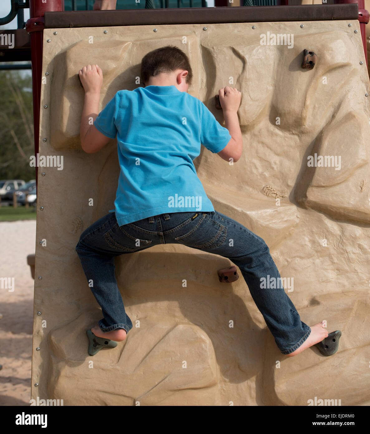 Eight year old boy climbing rock wall at park playground - Stock Image