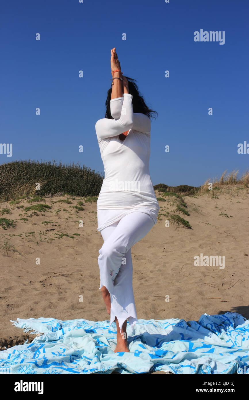 Garudasana , eagle pose woman practicing yoga on the beach - Stock Image