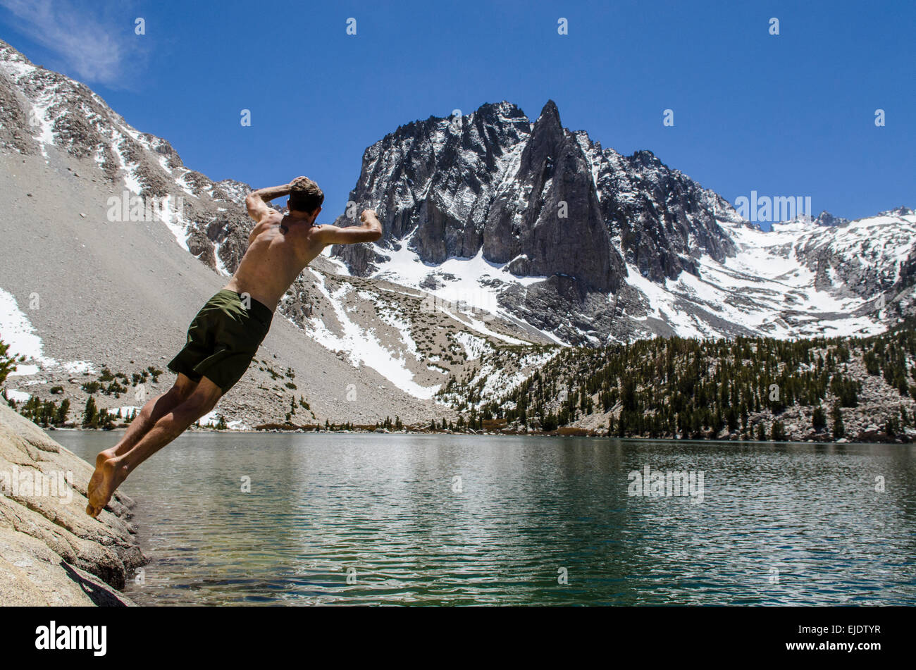 Cannonball time, a young man jumps in a desolation lake in the John Muir Wilderness, Eastern Sierras, California. - Stock Image