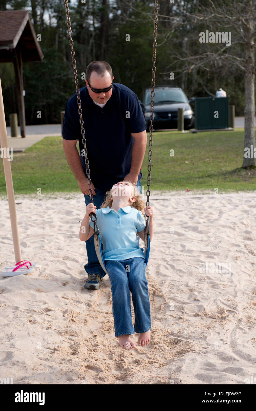 Father swinging his four year old daughter at a park playground - Stock Image