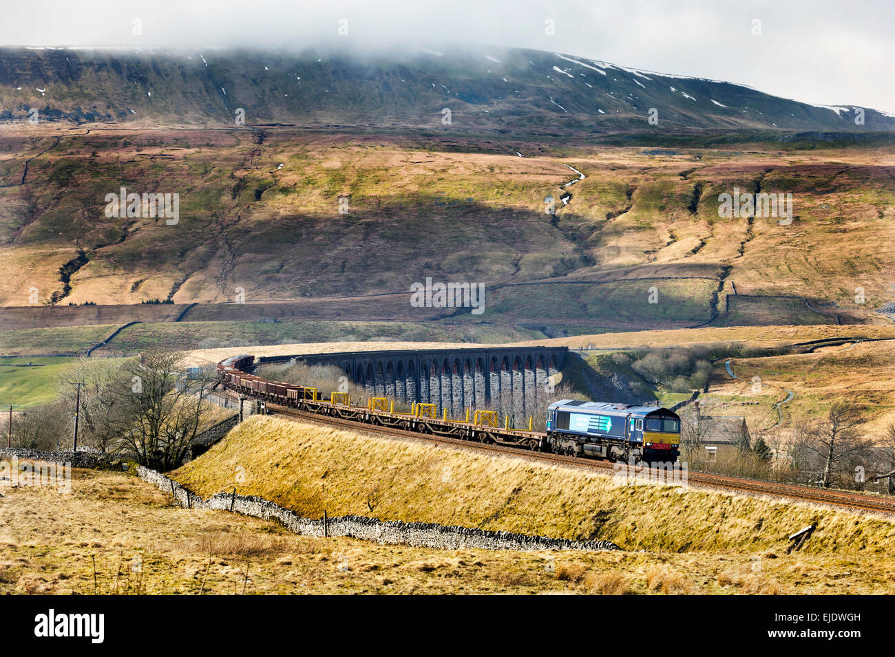A freight train leaves Ribblehead Viaduct on the Settle to Carlisle railway line, North Yorkshire. Whernside in - Stock Image