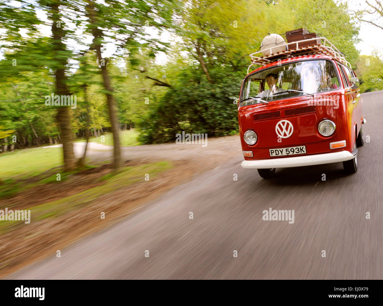 A red Volkswagen Camper bus on country road of East Sussex UK. - Stock Image