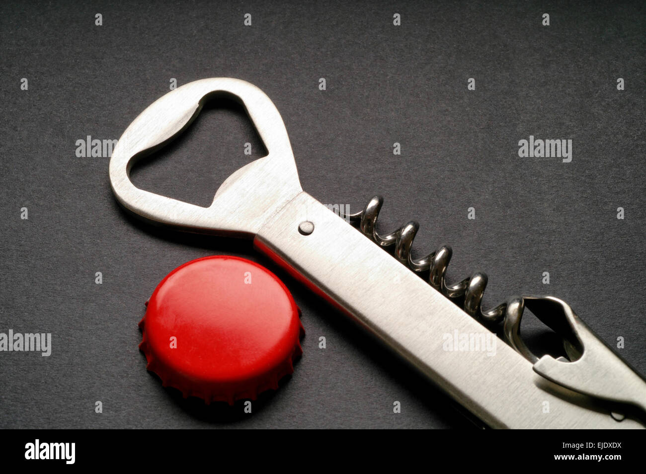 Steel corkscrew and bottle opener with red crown cap - Stock Image