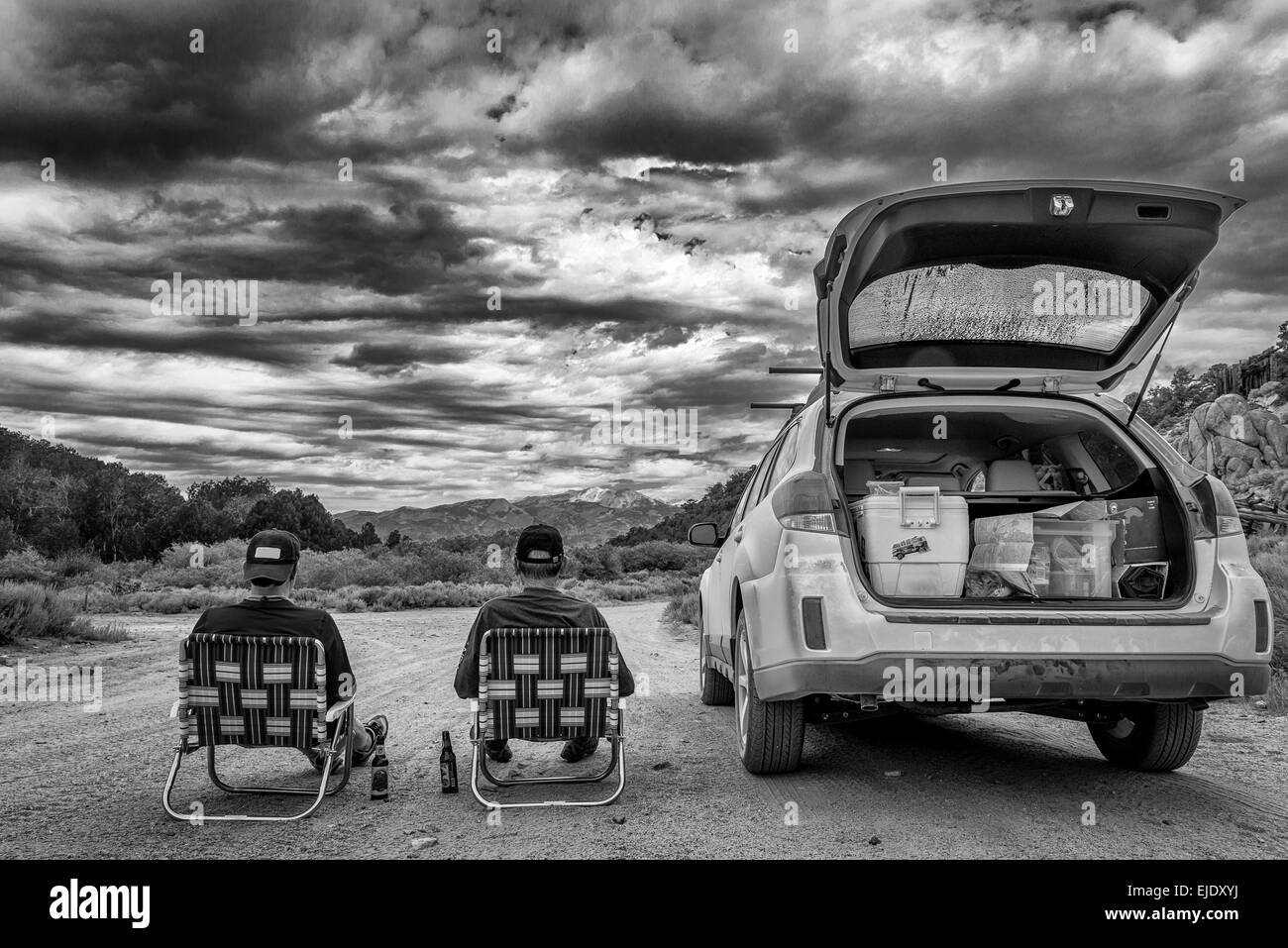 Two men sitting next to a Subaru Outback in black and white Stock Photo