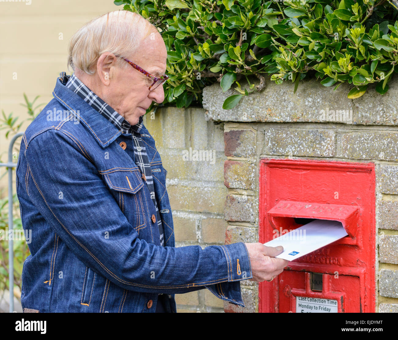 Elderly man posting a letter in a Royal Mail wall mounted letter box, in England, UK. - Stock Image