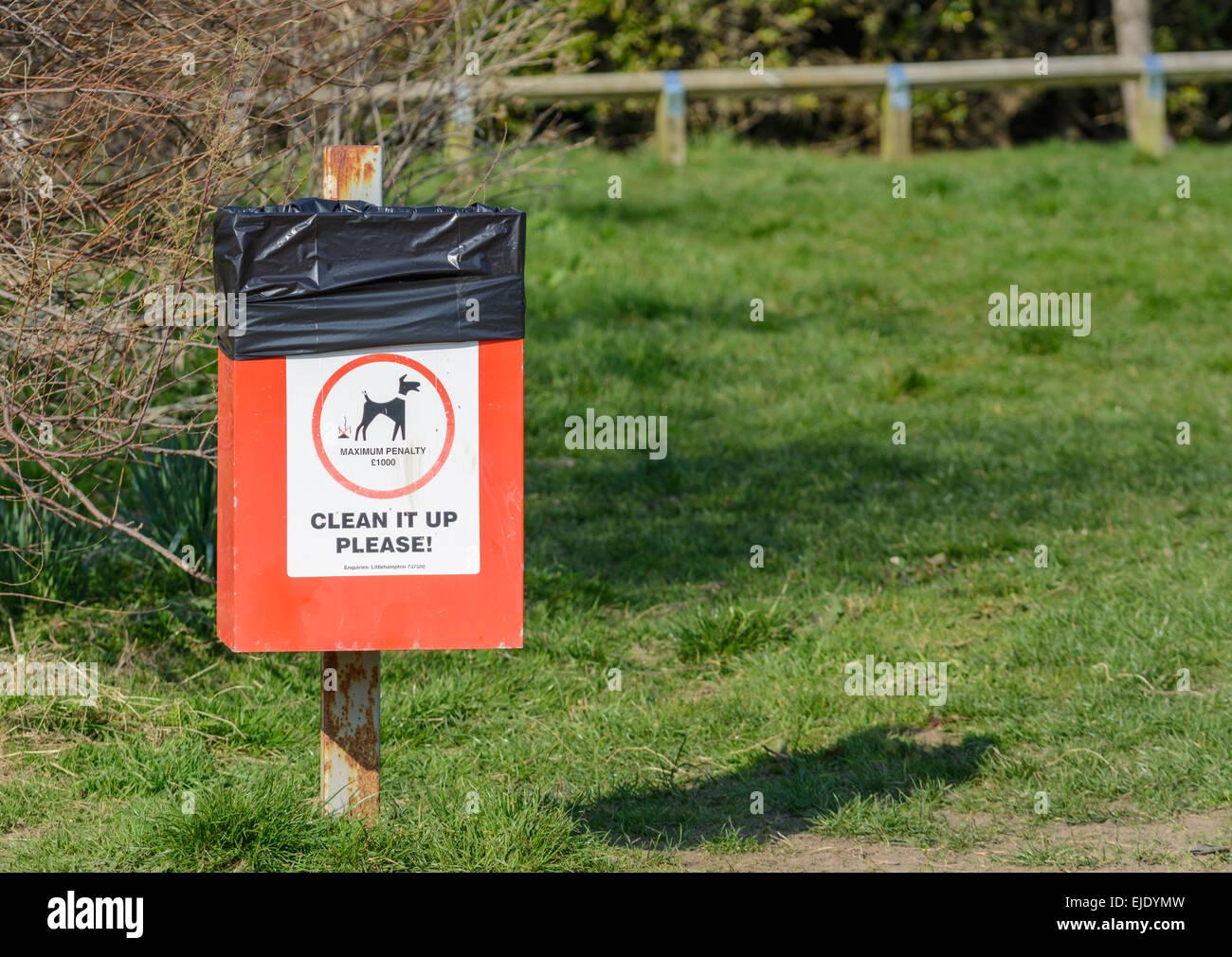 Dog waste bin in a park in the UK. - Stock Image