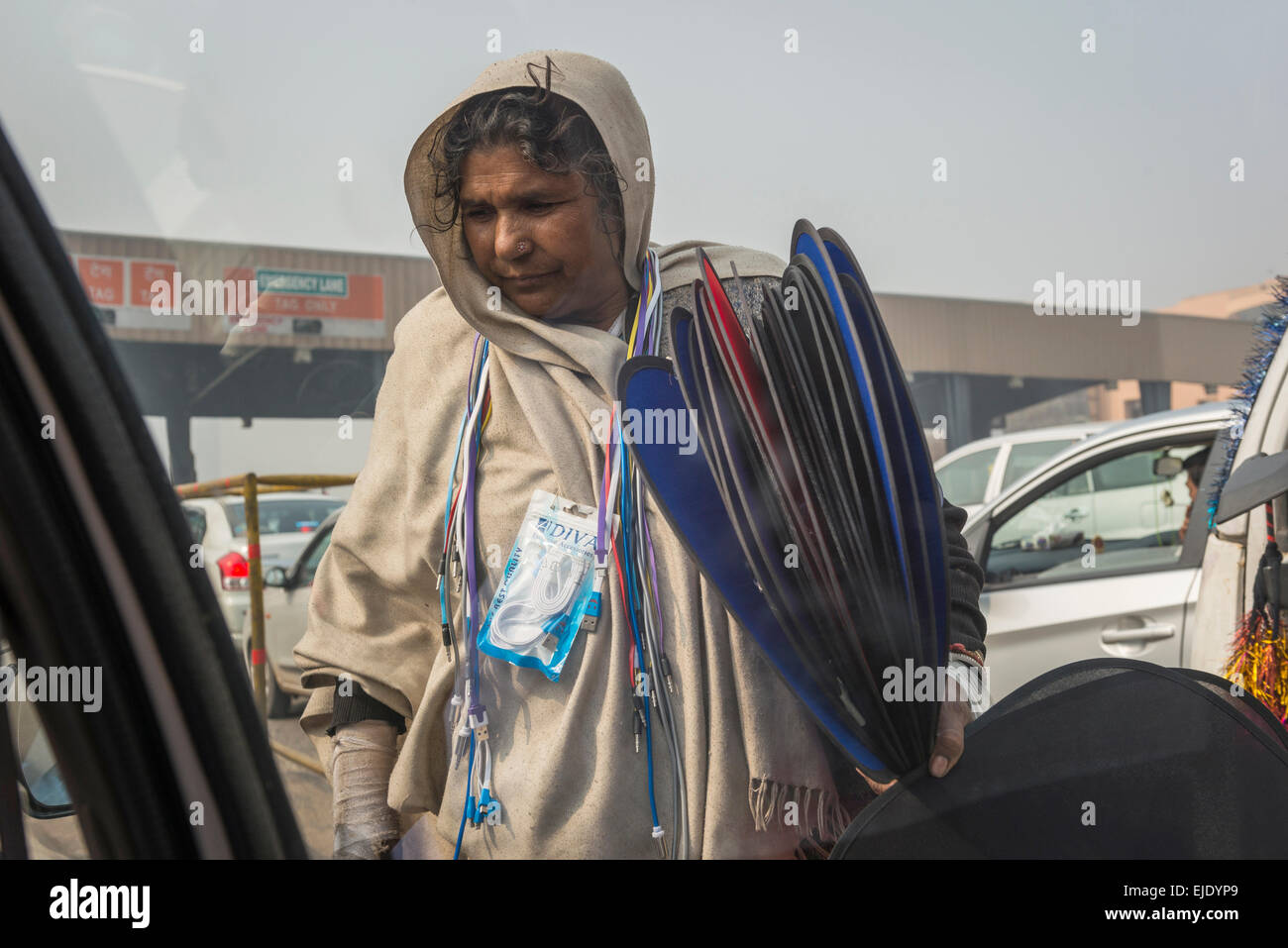 Woman selling mobile phone chargers and sun screens at a road toll on an Indian motorway - Stock Image