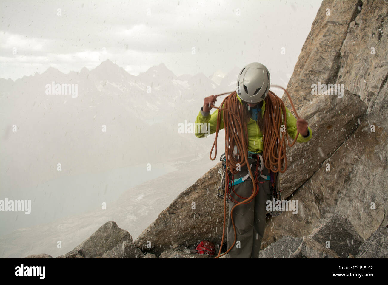 A woma coiling a rope in a storm, Titcomb Basin, WInd River Range, Pinedale, Wyoming. - Stock Image