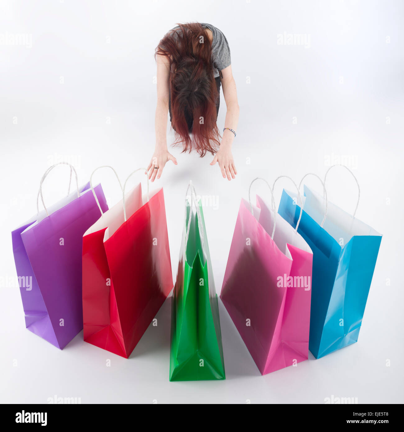 Woman Bowing on Floor In Front of Shopping Bags - Stock Image