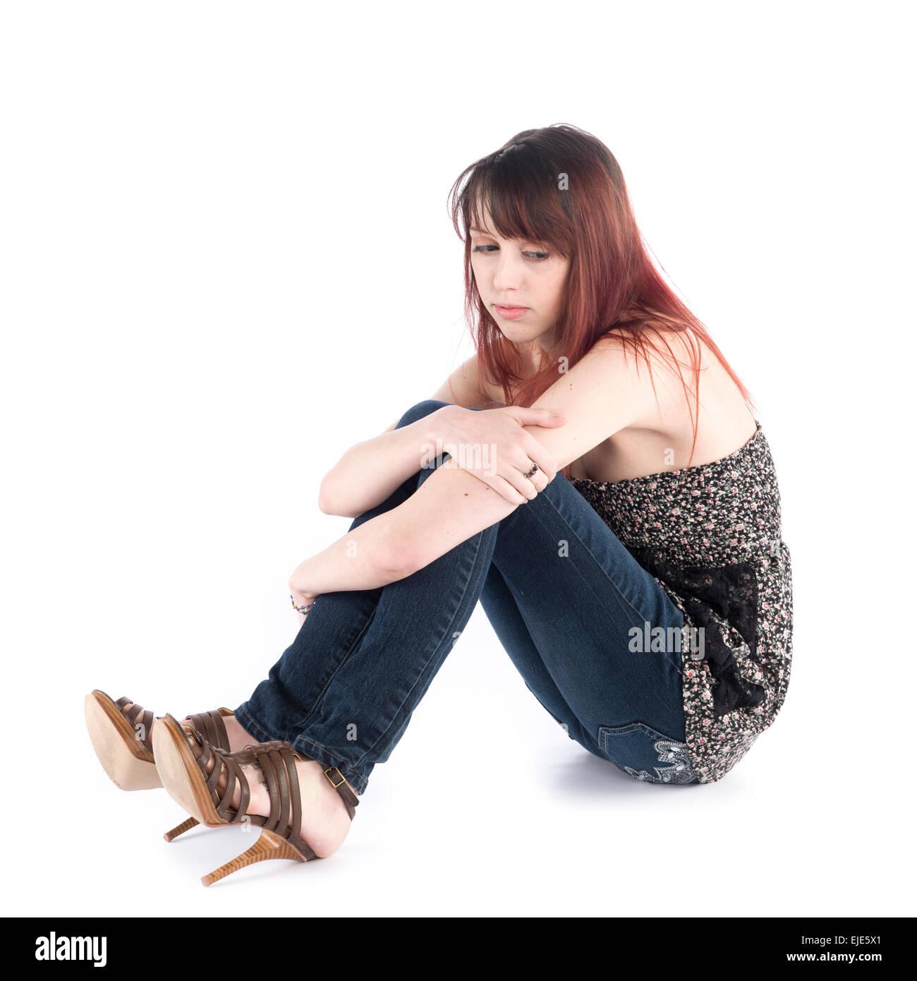 Sad Woman Sitting on the Floor Embracing her Knee - Stock Image