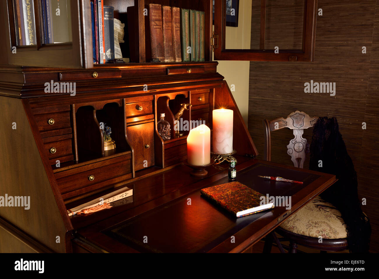 Classic wood secretary writing desk in dark room with candles and chair - Stock Image
