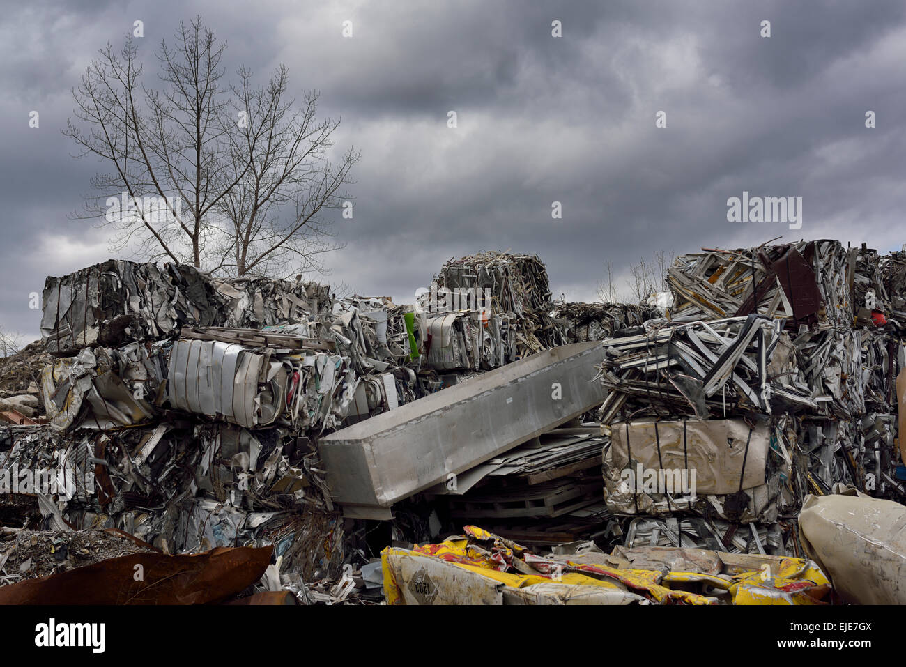 Heap of cubes of crushed recycled scrap metal junk with clouds and tree in Spring Toronto - Stock Image