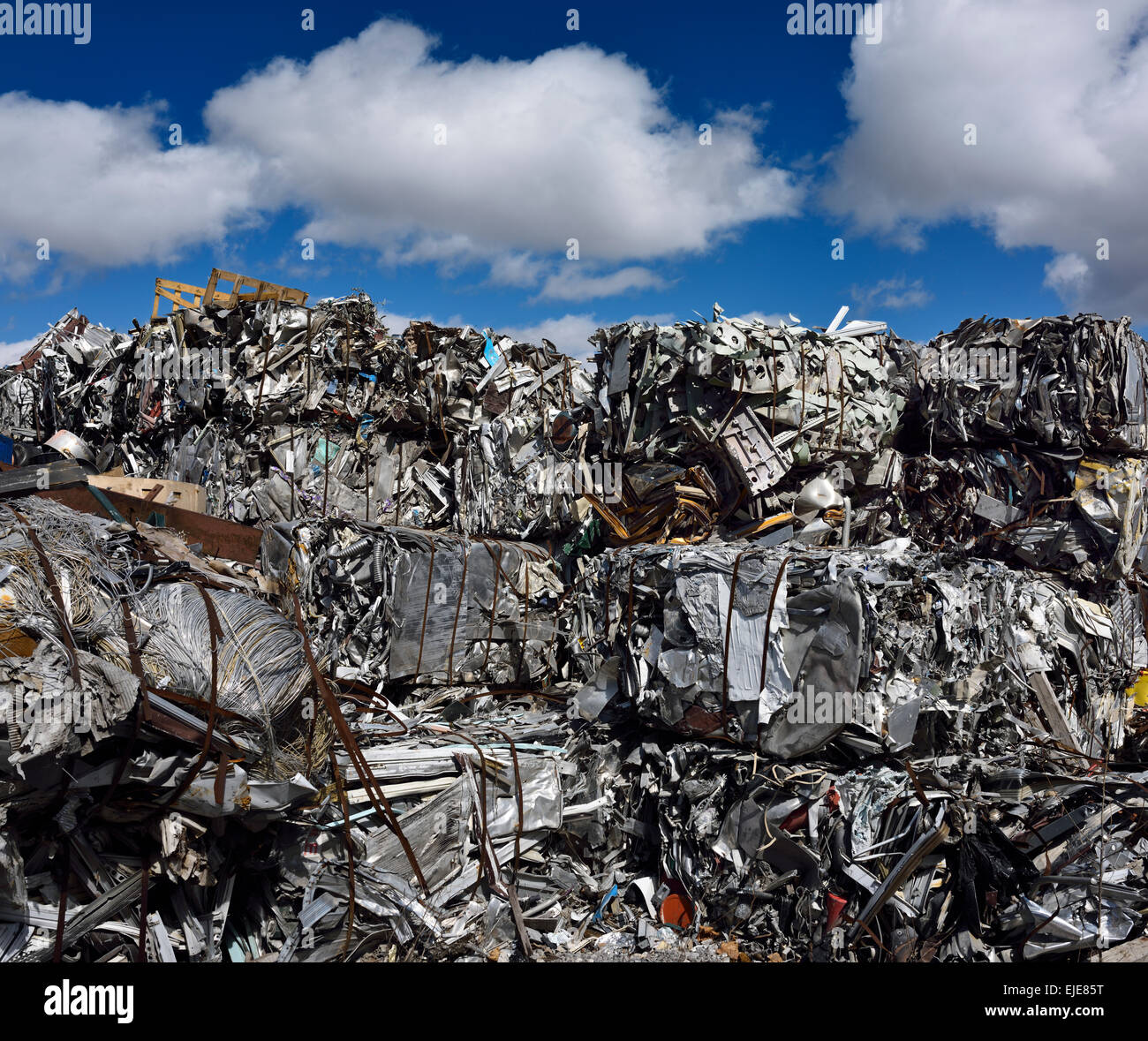 Mountain of crushed recycled scrap metal cubes with blue sky and clouds Toronto - Stock Image