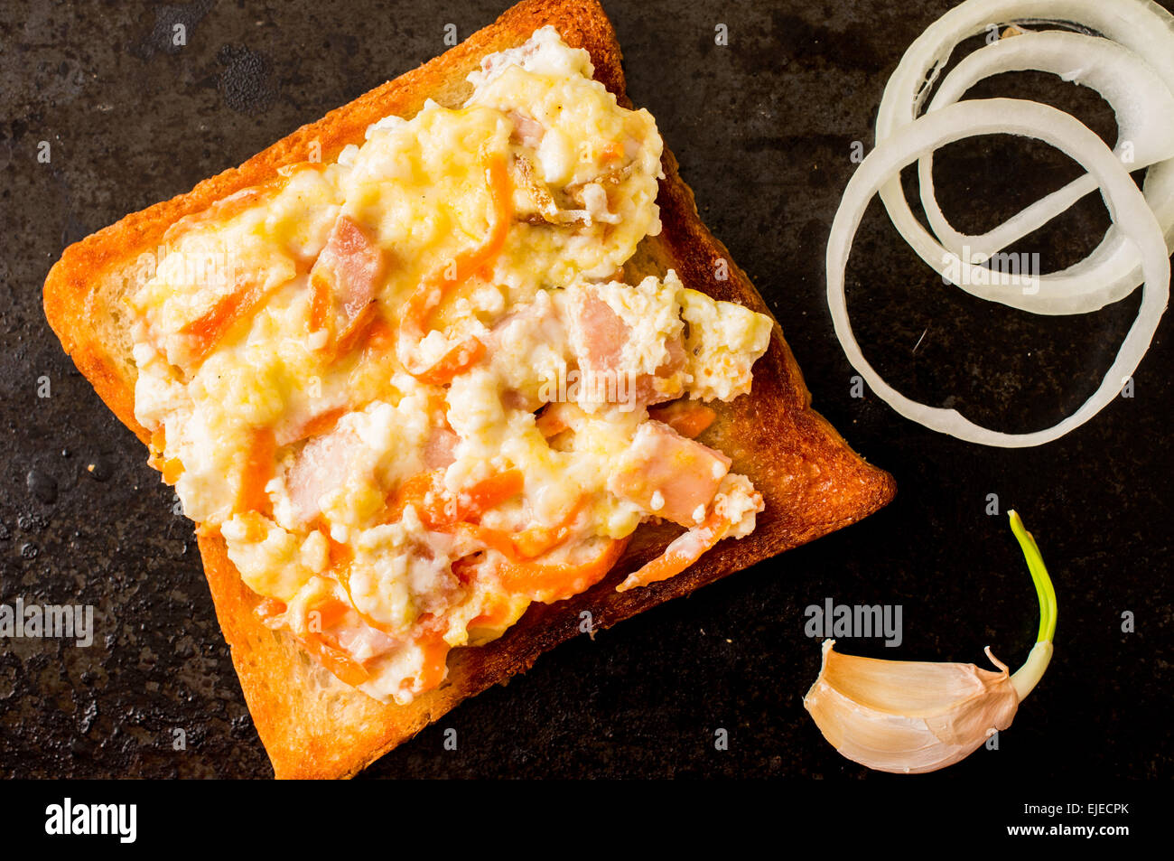 Sandwich with scrambled eggs on a black surface with onion and garlic - Stock Image