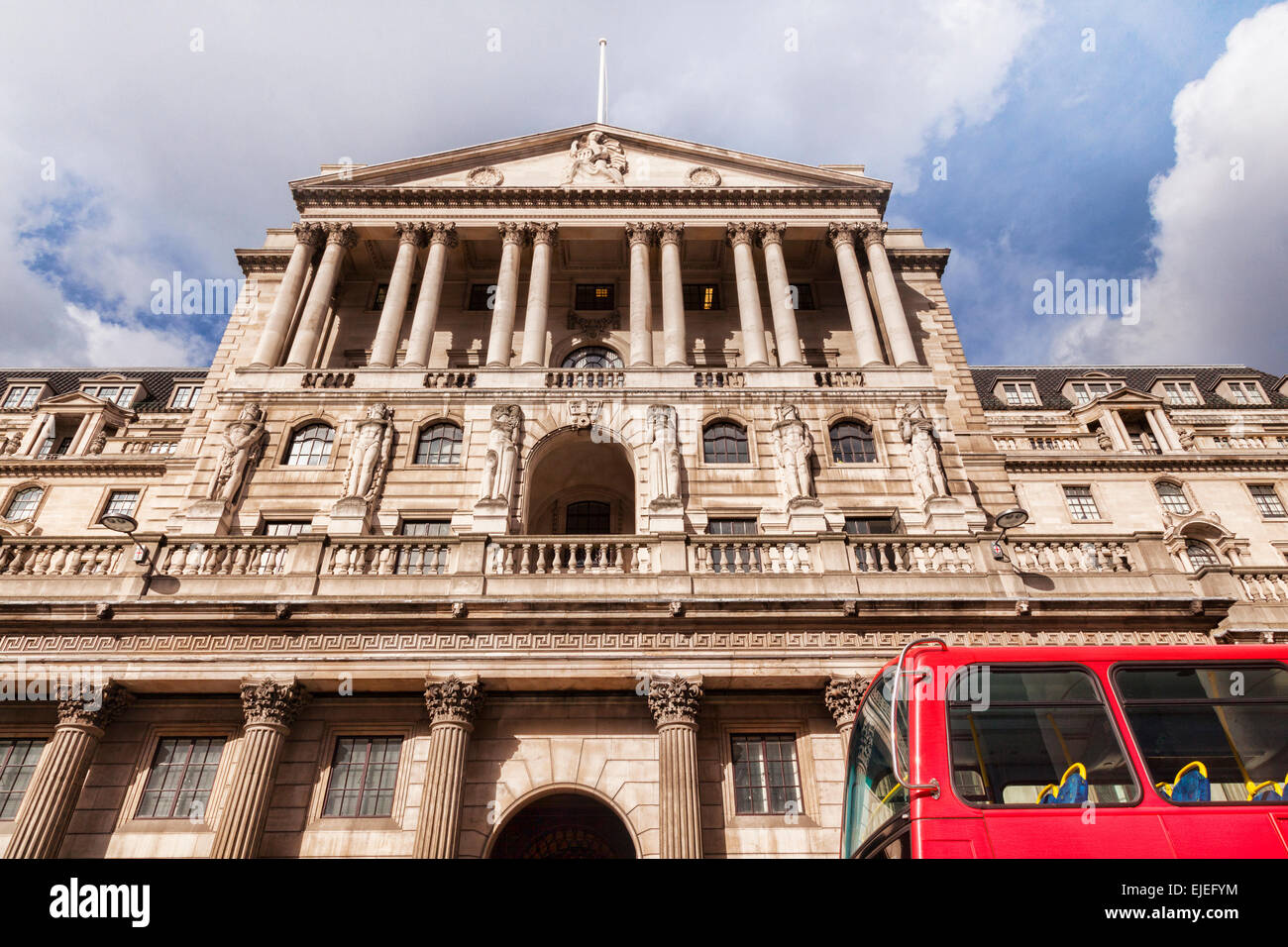 Bank of England, Threadneedle Street, London, England, with a red London bus just passing by. - Stock Image