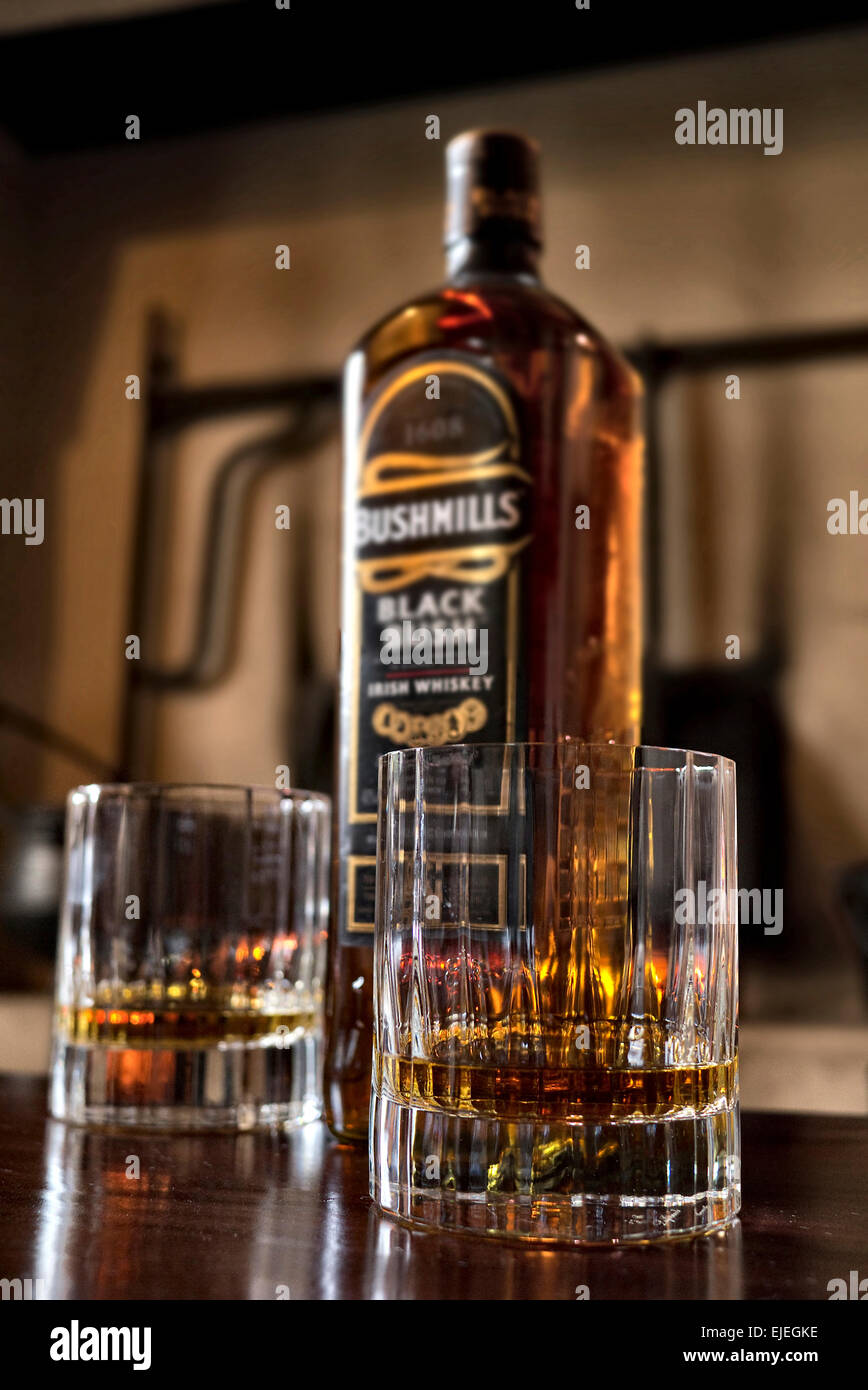 Two glasses of Bushmills  Black Bush Whiskey with bottle on a bar - Stock Image
