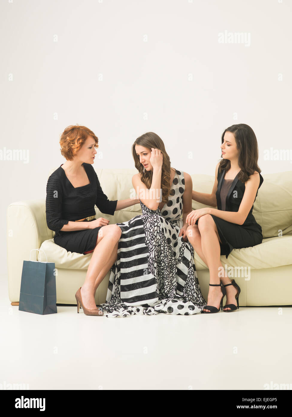 two beautiful young women sitting on sofa, comforting another while she worries not having money to buy a dress - Stock Image