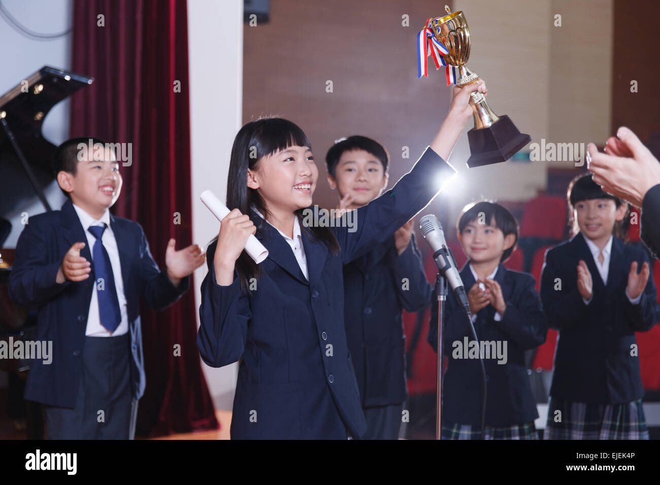 Excited schoolchildren waving arms holding a trophy - Stock Image