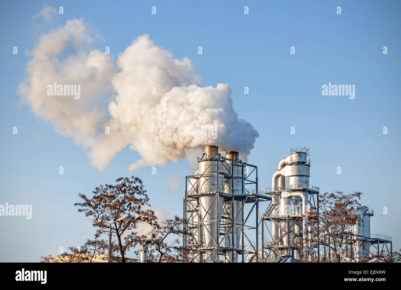 Smoking chimneys over blue sky, air pollution concept. - Stock Image