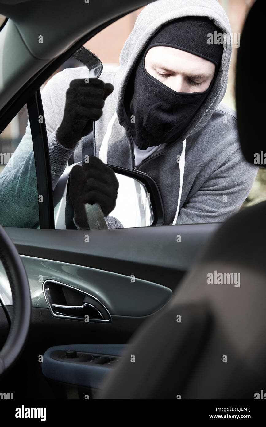 Masked Man Breaking Into Car With Crowbar - Stock Image