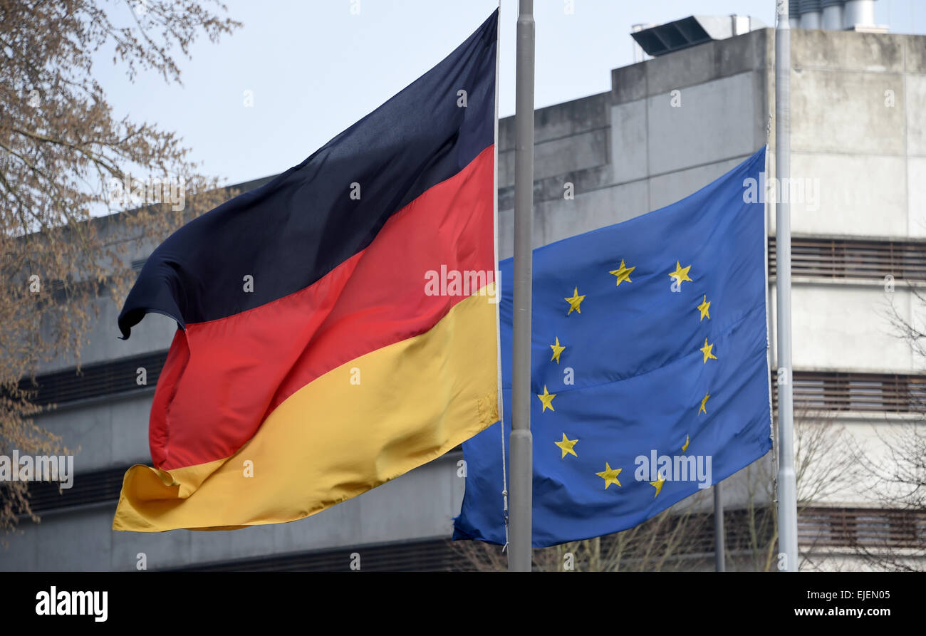 Kiel, Germany. 25th Mar, 2015. The German (L) and European Union flags fly at half mast in honor of the victims - Stock Image