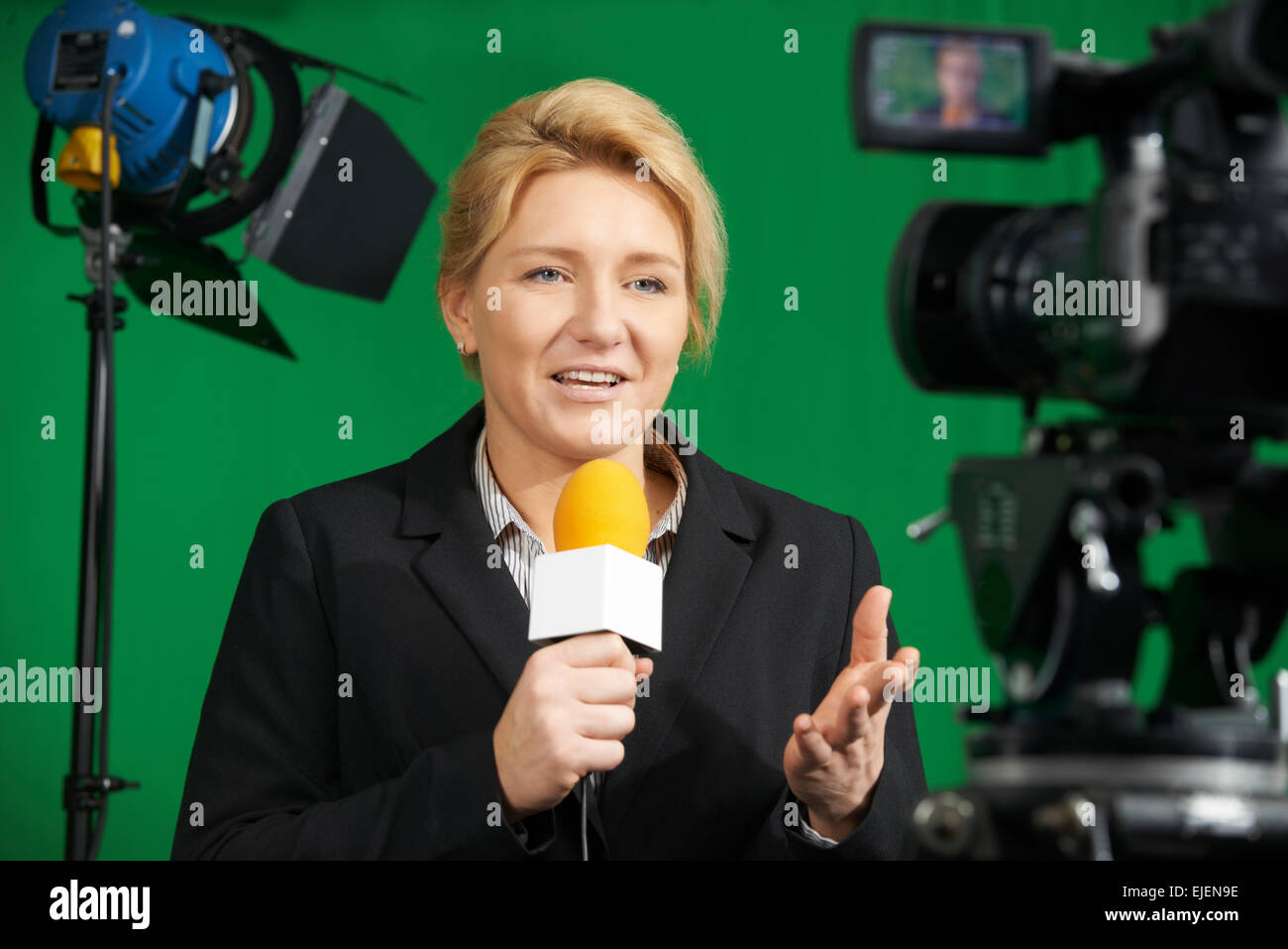 Female Journalist Presenting Report In Television Studio - Stock Image
