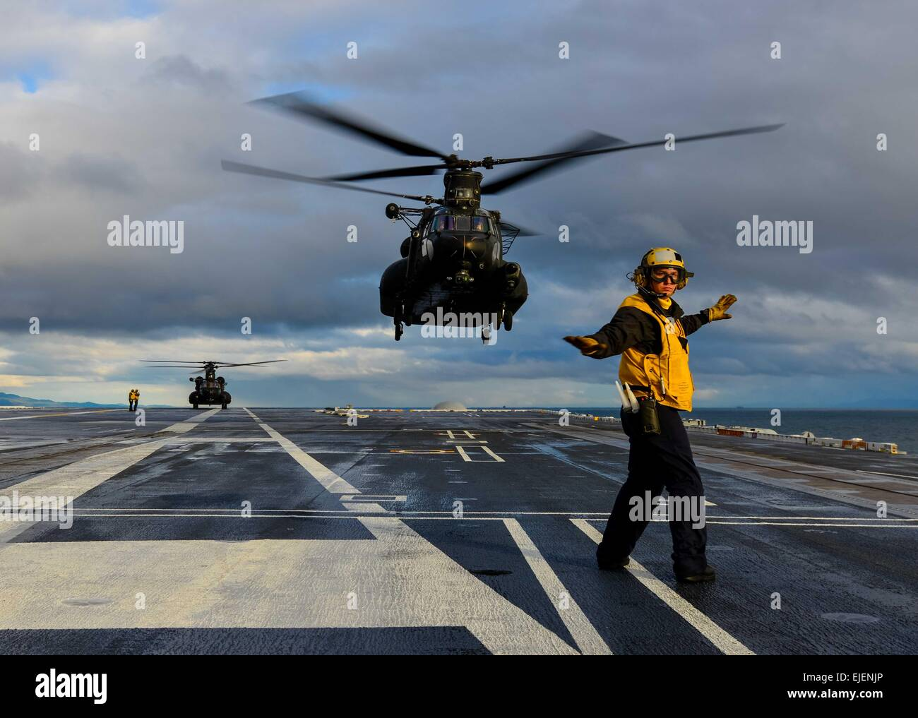 A US Navy sailor performs a safety check before signaling for the take off of an Army CH-47 Chinook from the flight - Stock Image